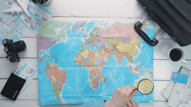 videoblocks-top-view-travelers-hands-looking-at-world-map-using-magnifying-glass-at-white-wooden-desk_s4zxex7j0ce_thumbnail-full01