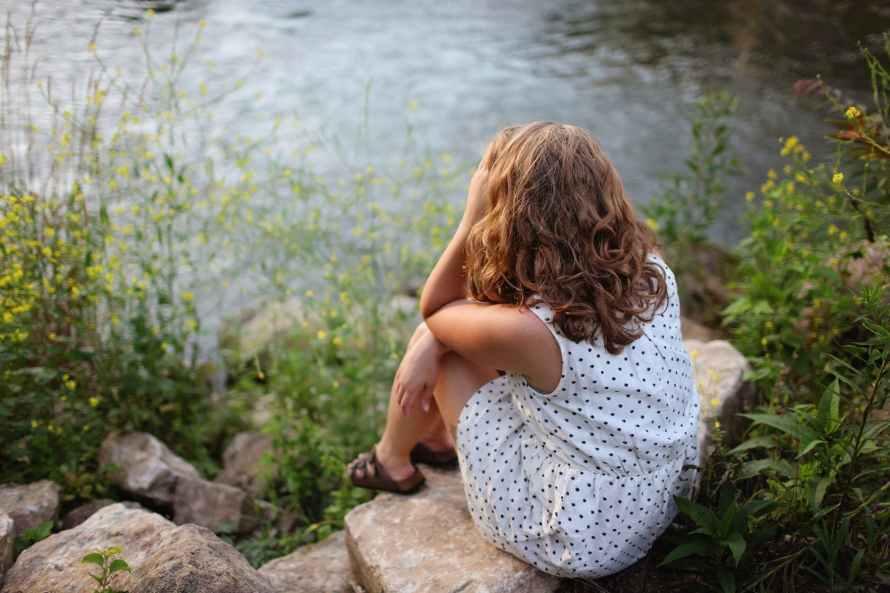 woman sitting by lake